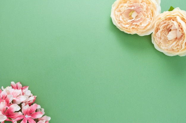 Spring background with flower composition on green board. festive frame or border. top view with copy space.