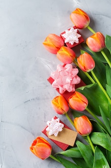 주황색 화려한 튤립과 선물 상자, 여성, 어머니의 날, 인사말 카드, 평평한 평신도 및 복사 공간 이미지가 있는 봄 배경