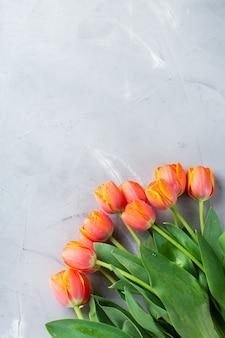 오렌지 화려한 튤립과 봄 배경입니다. 여성, 어머니의 날, 인사말 카드, 평평한 평신도 및 복사 공간 이미지