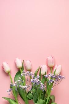 青い背景にピンクのチューリップの春のバナー。花柄。