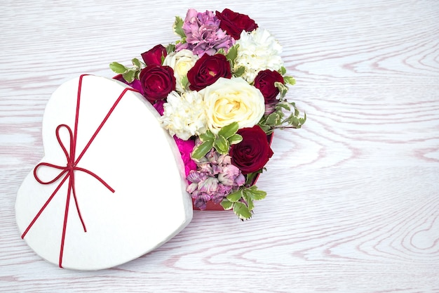 Spring banner roses bouquet in the box on the white wooden background, greeting card with copy space.