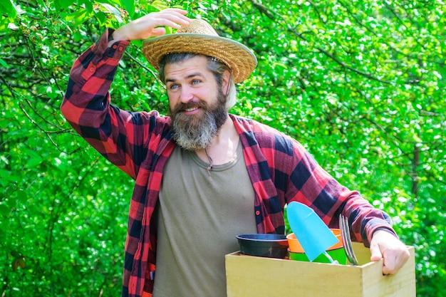 春。ガーデニングツールを持つひげを生やした男。庭で幸せな農夫。ガーデニングツールを持つ庭師。