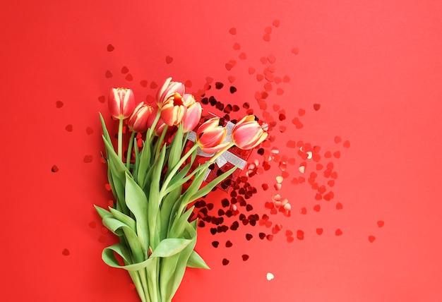 작은 하트 반짝이와 붉은 밝은 배경에 봄 아름 다운 튤립 꽃. 어머니의 날, 인사말 카드 축제 장식 꽃 구성.
