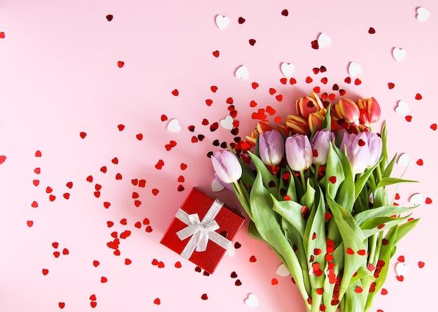 붉은 하트 반짝이와 부드러운 파스텔 핑크 배경에 봄 아름 다운 튤립 꽃. 어머니의 날, 인사말 카드 축제 장식 꽃 구성.