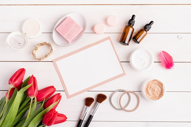 Spring and beauty cosmetics. top view of cosmetics with pink tulips top view flat lay on white wooden background, flat lay