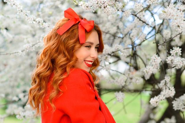 긴 붉은 머리를 야외에서 불고 봄 아름다움 소녀. 피는 나무. 로맨틱 젊은 여성의 초상화입니다. 자연