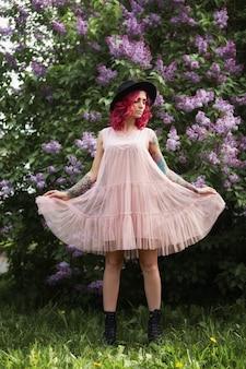 Весенний портрет красоты красивой девушки с рыжими волосами в ветвях цветущей сирени. сиреневые цветы в руках и волосах женщины