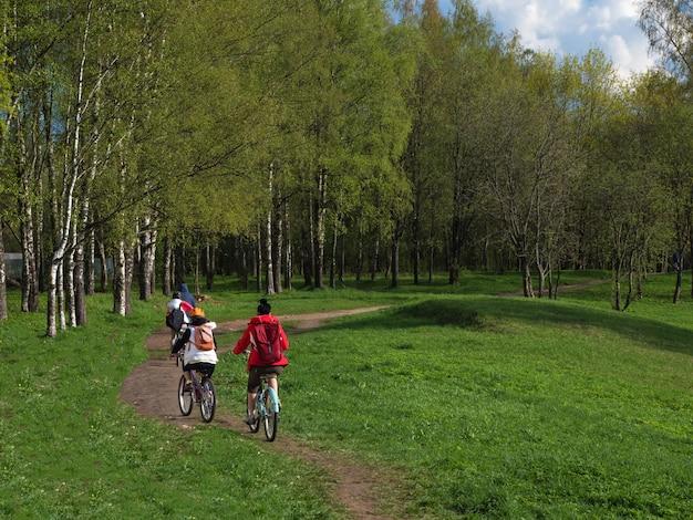 春の自転車は自然の中で家族全員と一緒に乗ります。公園を散歩している家族のサイクリスト。