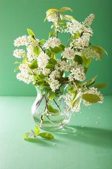 緑の背景の上の花瓶に春の鳥桜