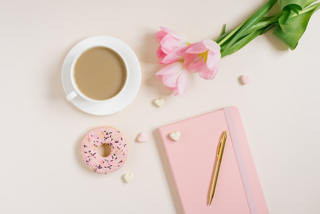 Spring blog concept. cup of cofee, donut and bouquet of pink tulips on beige background. flat lay, top view feminine desk.