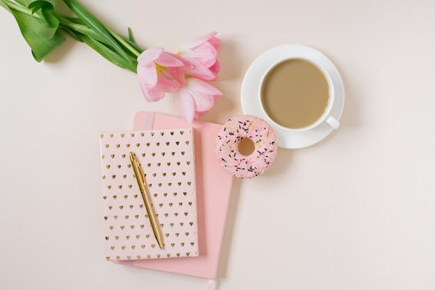 Концепция весеннего блога. чашка кофе, пончик и букет розовых тюльпанов на бежевом фоне. плоский женский стол, вид сверху.