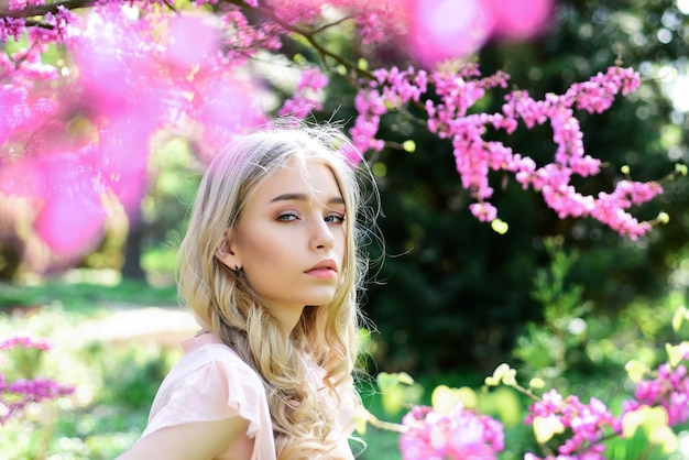 Spring bloom concept. beautiful female face with perfect skin. girl on dreamy face, tender blonde near violet flowers of judas tree, nature background. beautiful young spring woman