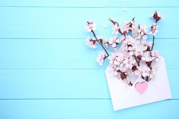 Copyspaceと青い木製の背景上の封筒に春咲く枝。