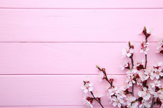 Copyspaceとピンクの木製の背景に春咲く枝。