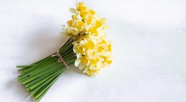 Весенние цветы, желтые нарциссы на светлом деревянном