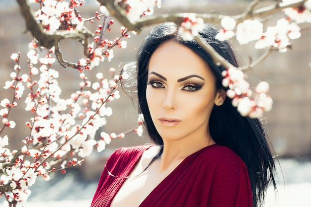 Spring blossom beauty woman near apricot blooming tree seasonal feature beauty and fashion