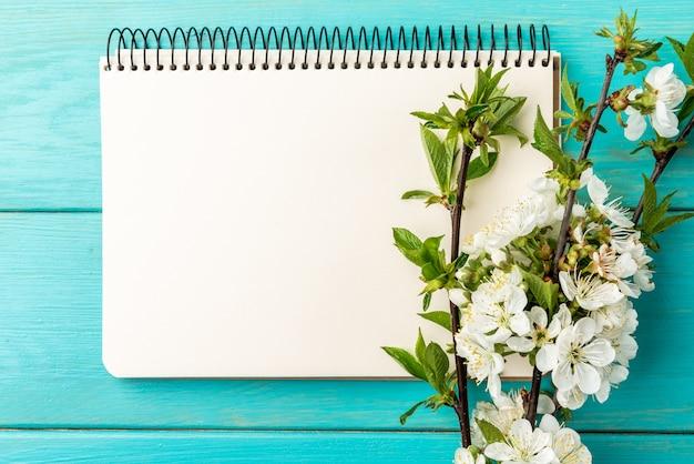 Ветви вишни цветения весны и тетрадь на голубой деревянной предпосылке.