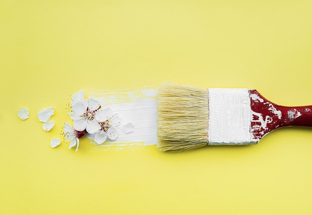 Spring blossom concept. paint brush with apricot blossom flower on yellow background.