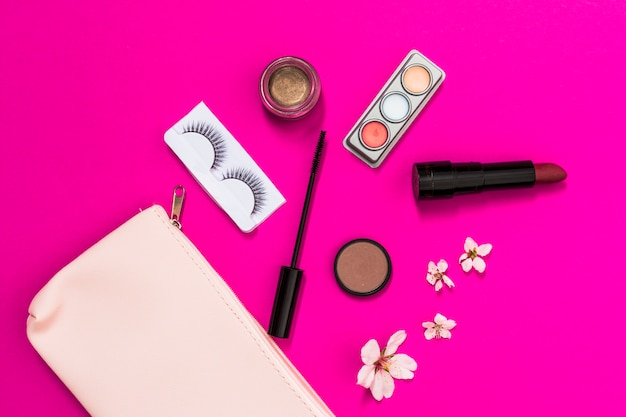봄의 꽃; 속눈썹; 아이 섀도우; 립스틱; 마스카라 브러쉬 및 분홍색 배경에 핑크 메이크업 가방 꽃
