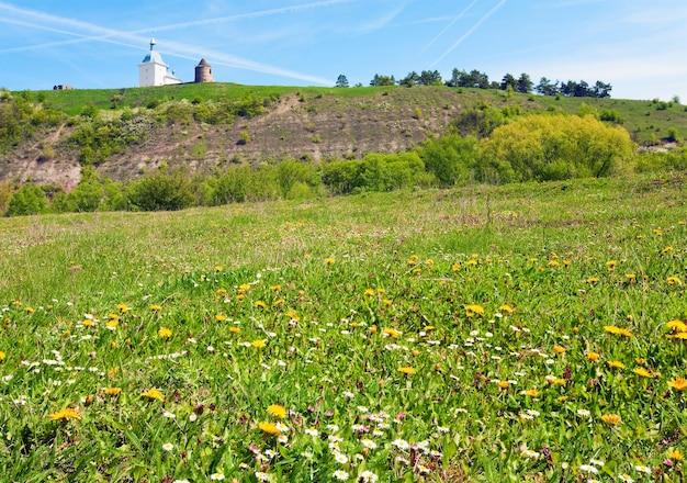 봄 꽃이 만발한 들판과 고대 fotess 및 뒤에 있는 교회(pidgora village, ternopilska oblast, ukraine의 변형 수도원, xvii-xviii 세기에 건물)