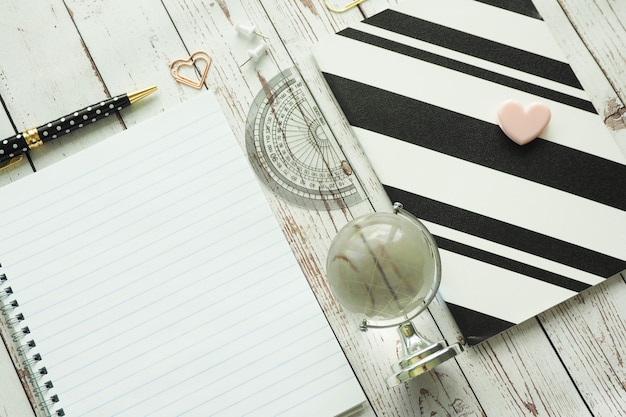 Spring book, black and white notebook, pen, paper clips and glass globe