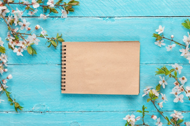 Spring border flowers cherry blossoming with blank paper notebook on blue wooden table. top view