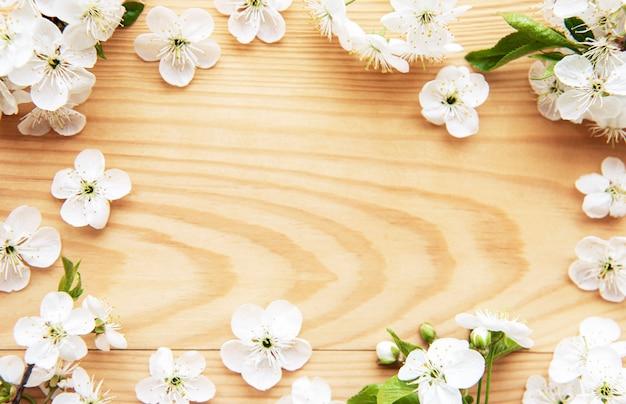 아름다운 흰색 꽃 가지와 봄 테두리 테이블. 나무 테이블에 섬세한 꽃이 피어납니다. 봄 개념. 평면 위치 평면도 복사 공간.