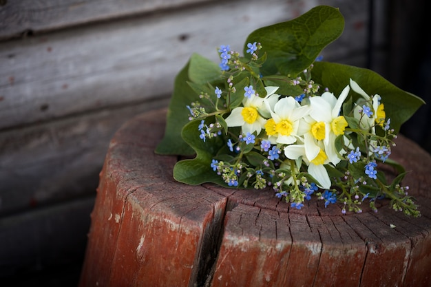 Spring bouquet of forget me not narcissus daffodils and leaves laying on the wooden background