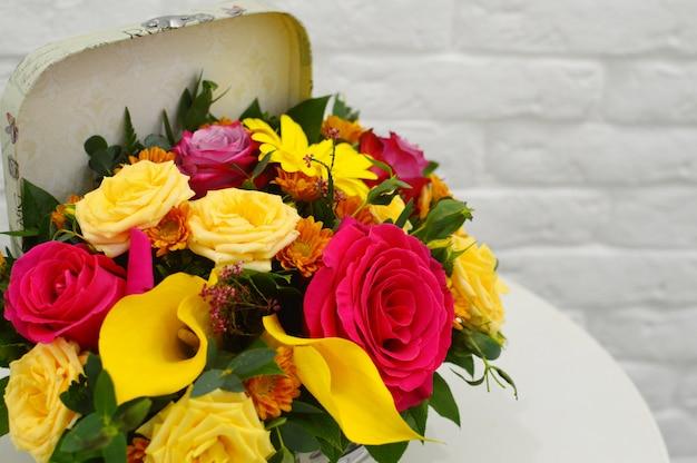 Весенний букет цветов в стильной шляпной коробке на белом столе.