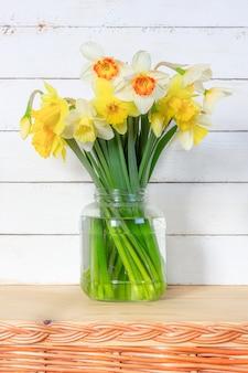 Весенний букет цветов нарцисса в стеклянной банке на крупном плане белой деревянной стены
