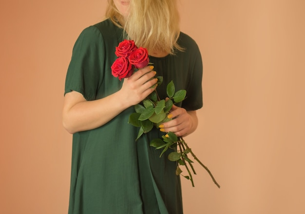 明るいベージュの背景に女性の手で赤いバラの春の花束