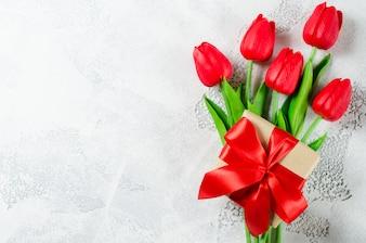 赤いチューリップとギフトボックスの春の花束。