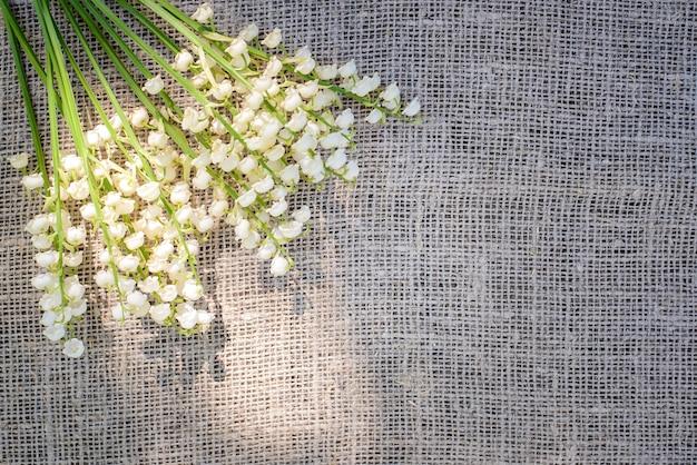 Весенний букет из белых ландышей на фоне мешковины, холст, ткань в солнечном свете, вид сверху, копия пространства