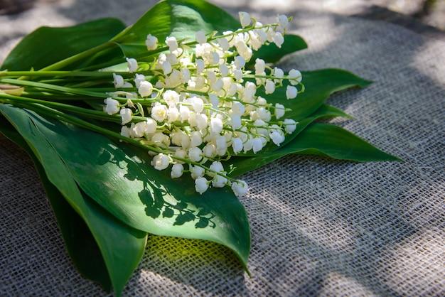 黄麻布、キャンバス生地の背景に白いユリの春の花束