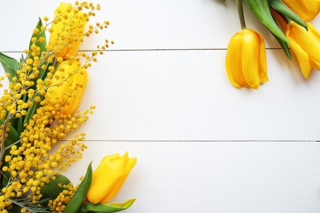 黄色いチューリップとミモザの花の春の花束。母の日、3月8日またはイースターのコンセプト。