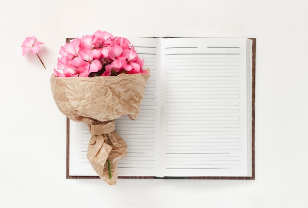 Spring bouquet of pink flowers in kraft wrapping paper with notebook