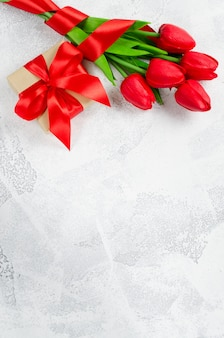 Spring bouquet of red tulips and gift box.