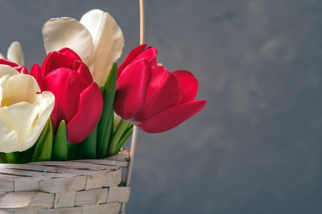Spring bouquet of tulips in basket on vintage backdrop.
