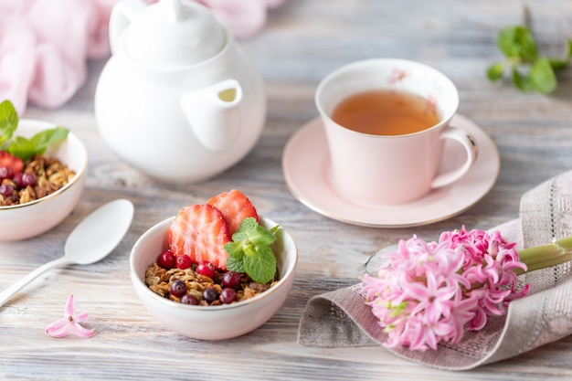 Spring breakfast with granola and fresh strawberries and lychee and flowers on wooden background.