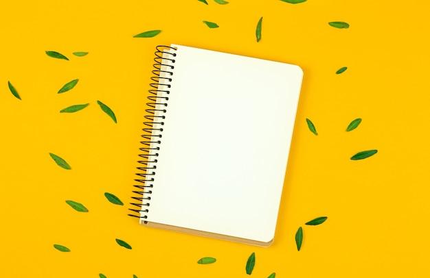 スケッチ、白紙、黄色のデスクトップ写真の緑の葉のためのnontepadと春のカードのモックアップ