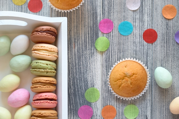 Spring celebration flat lay with macarons, muffins and marzipan eggs jn a decorative tray on grey wood