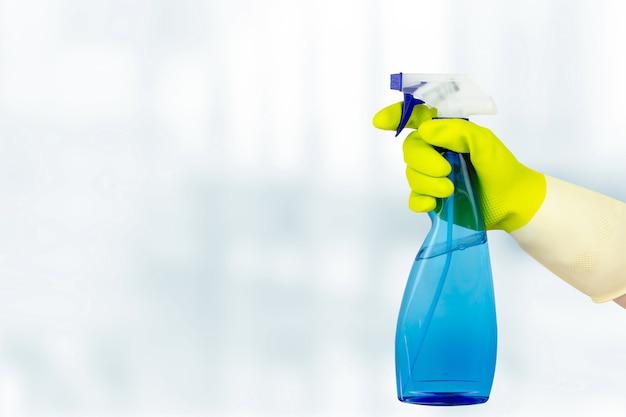 Концепция весенней уборки. рука держа бутылку с распылителем. женщина, держащая бутылку моющего средства на белом фоне. генеральная или регулярная уборка.