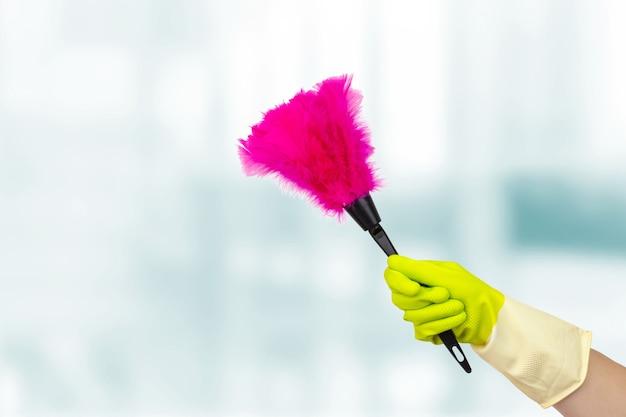 Концепция весенней уборки. рука с мягкой пурпурной тряпкой, веник из синтетических перьев. рука женщины держа тряпку чистой. концепция клининговых услуг.