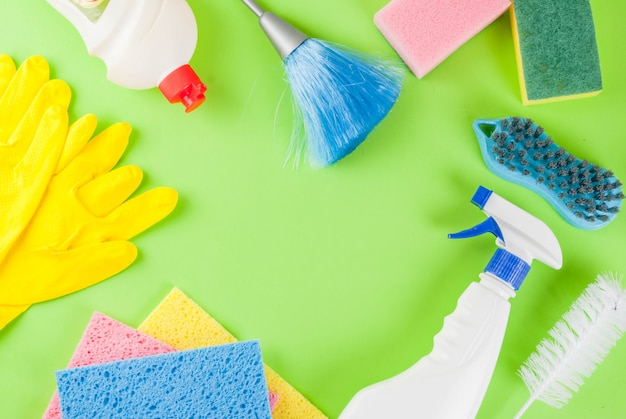 Spring cleaning concept with supplies, house cleaning products pile. household chore concept, on green  top view  copyspace frame