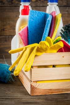 Spring cleaning concept with supplies, house cleaning products pile. household chore concept, on rustic or garden wooden background copy space