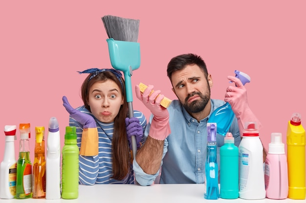Concetto di pulizia primaverile. inquadratura orizzontale di marito e moglie tenere detersivo spray, circondato da prodotti per la pulizia, utilizzare scopa, indossa guanti di gomma per la protezione delle mani, pulire insieme la casa
