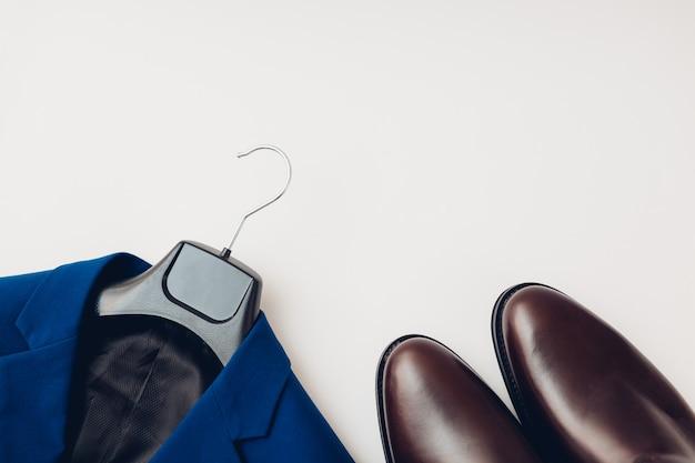 春の服装と靴、男性用のチェルシーレザーブーツ。ハンガーに男性の古典的な青い色のファッショナブルなジャケット。