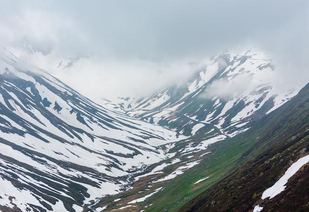 春の曇りの曇りの山の風景(スイス、オーバーアルプ峠)