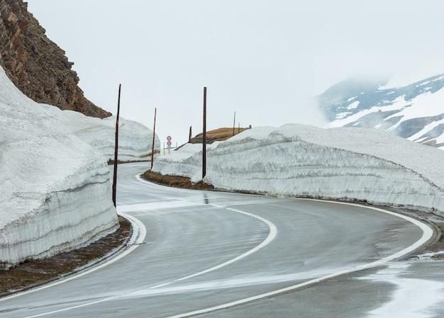 スイスのフルカ峠の曲がりくねった道と春の曇りの曇りの山の風景。