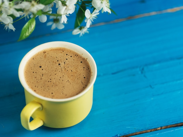 Spring coffee . yellow cup on blue background and cherry blossoms